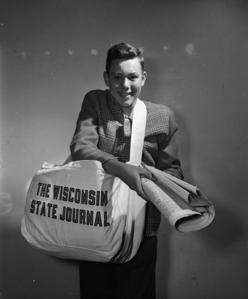 Portrait of Robert Stephen Goddertz, a Wisconsin State Journall newspaper delivery boy, wearing a large delivery bag and extending a newspaper toward the camera. WHI ID 54821