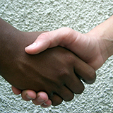 Close-up of caucasian and African-American hands shaking