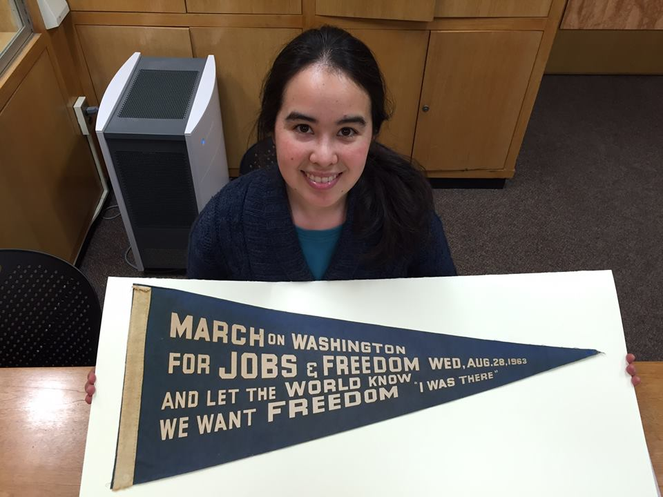 Archivist Lydia Tang shows off pennant from 1968 March on Washington