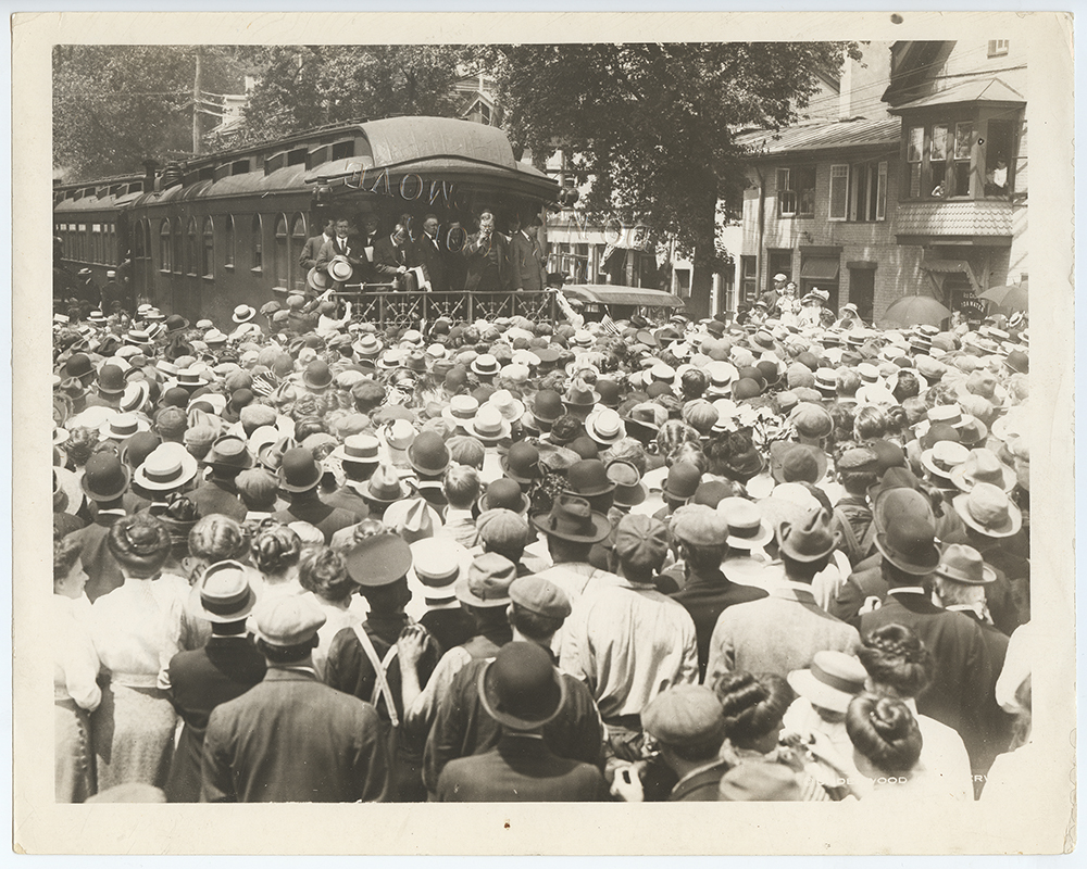 Theodore Roosevelt, standing on the end of a train car, delivers a speech to a large crowd.