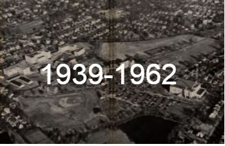 "Black and white aerial photograph with the words ""1939-1962"" overlaid on top of it"