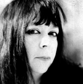 Black and white image of a white woman with black hair and brown eyes looking sideways into the camera