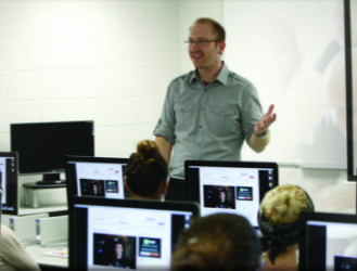 Image of person speaking in front of a group of students with computers