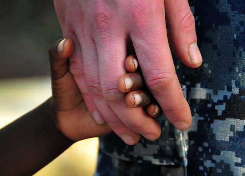 A white adult hand holding a small black child's hand