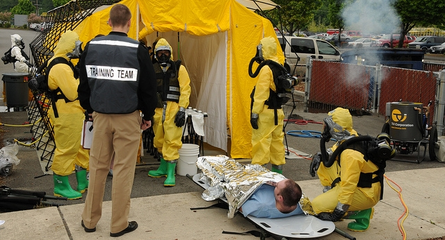 People in yellow hazard suits standing outside a yellow tent and tending to a  person lying on a stretcher