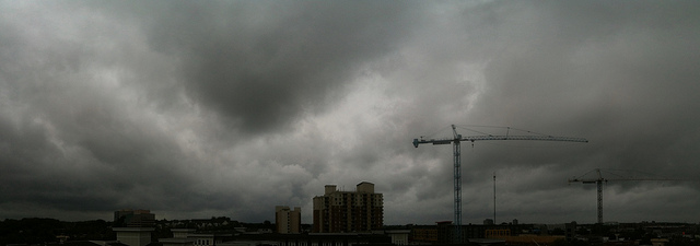 Stormy skies with construction cranes in the background