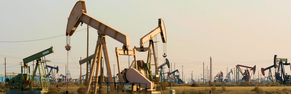 photo showing over 10 oil well pump jacks with two in the foreground and more in the distance