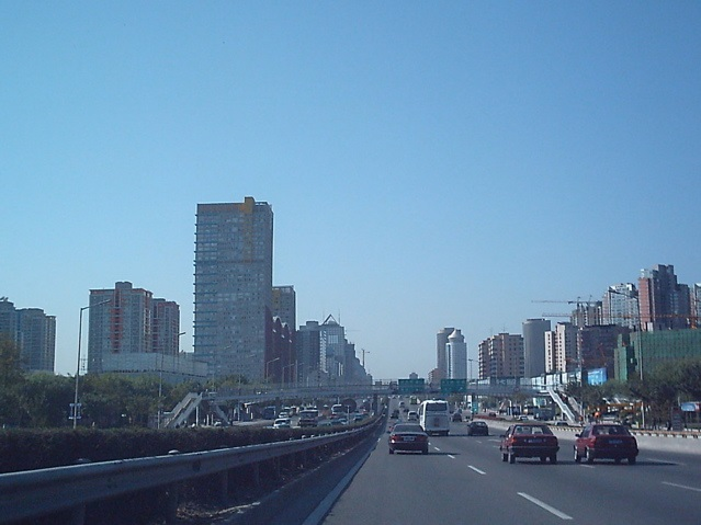 Beijing skyline showing cars driving away from the viewer and tall skyscrapers in the background