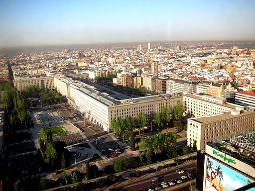 Madrid skyline showing large rectangular tan buildings in a block formation in the foreground and some taller buildings with red roofs in the background