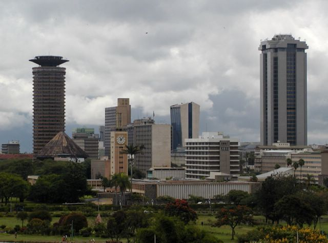 Nairobi cityscape showing two large skyscrapers, one on the left and one on the right, with shorter buildings between them and a cloudy sky behind.