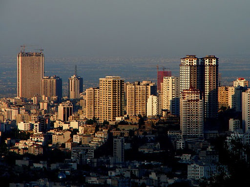 Tehran skyline showing many skyscrapers close together and a dusky blue sky behind.