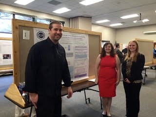 3 previous presenters at the fair showing off their poster