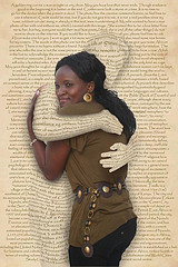 a person embracing another person from behind a printed page
