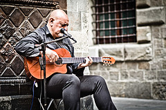 Street musician playing guitar with microphone
