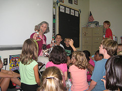 teacher displaying items to students in a classroom