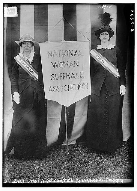 "Two suffragists holding a banner that reads ""National Woman Suffrage Association"""