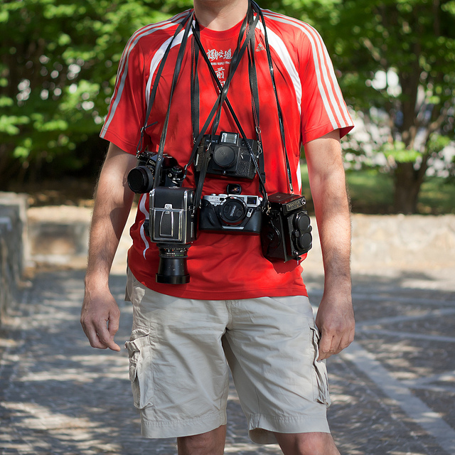 Man standing with several cameras hanging around his neck. Cannot see man's face.