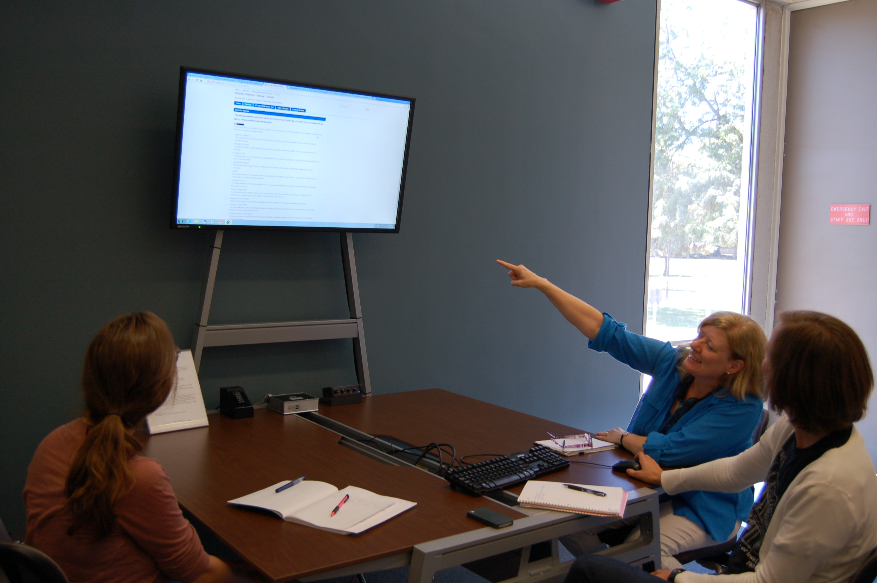 Patrons using the collaborative work station table and attached tv monitor