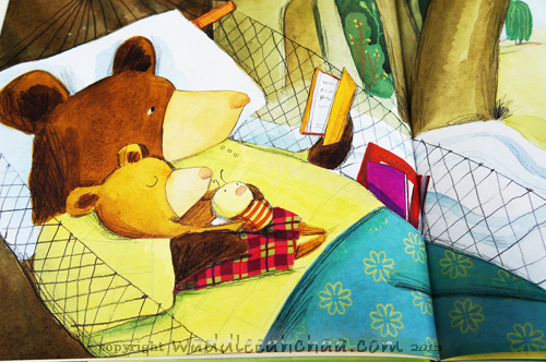 little bear tucked into bed with a book.