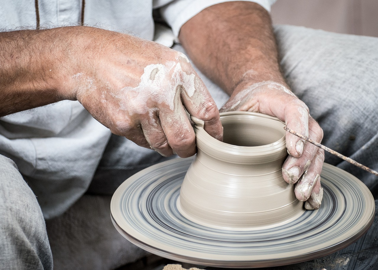 potter hands creating clay pot