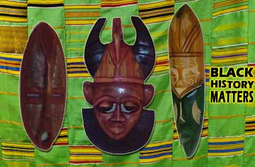 Three carved wooden masks from Ghana, in front of a kente cloth