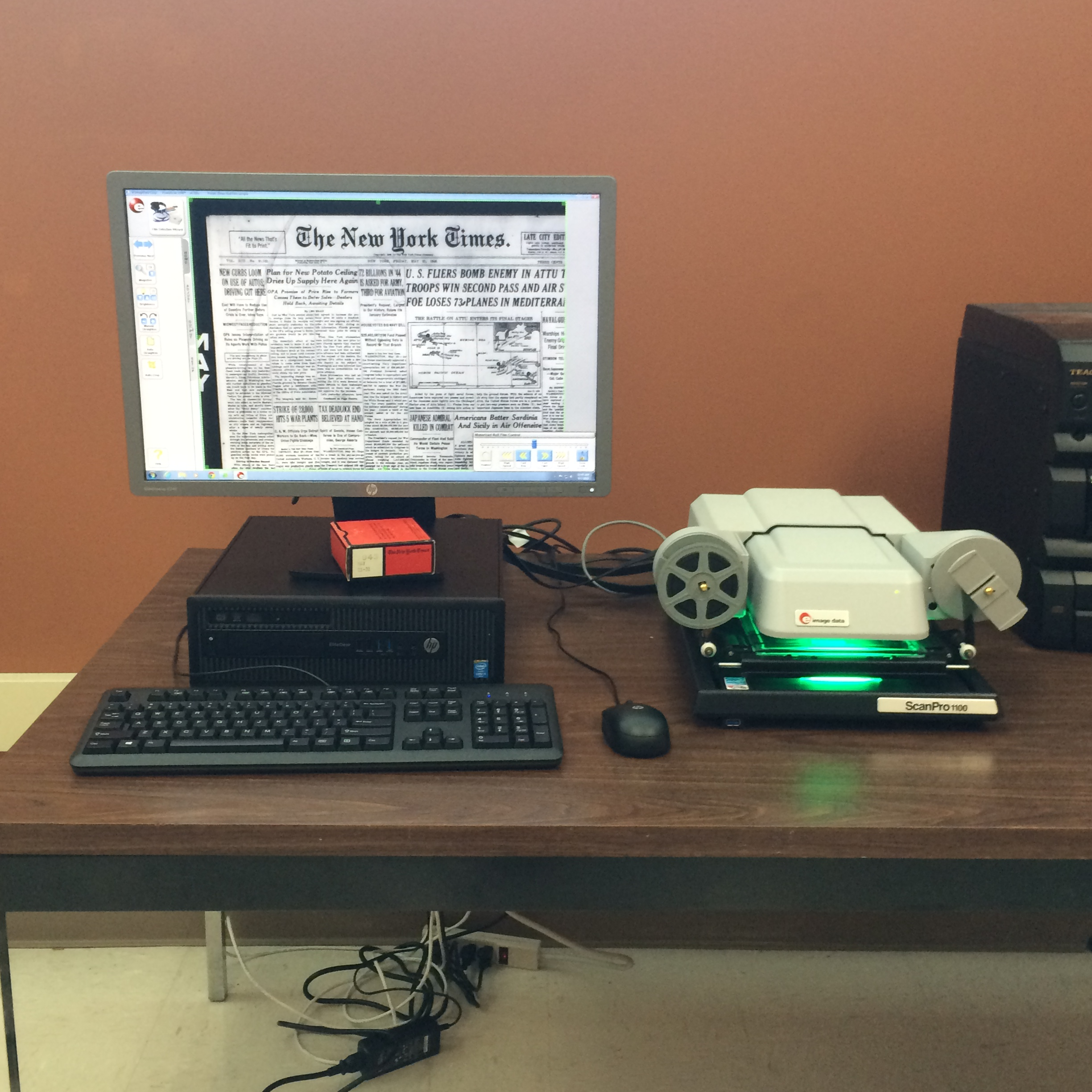 photo of microfilm reader next to a computer displaying new york times on microfilm