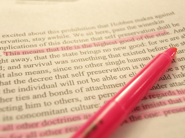 Pink highlighter highlighting text in book.