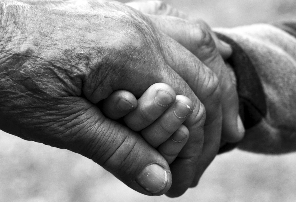 old and young person's hands clasped