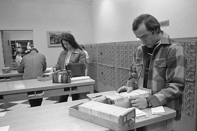 Three UNO students standing at tables searching in the library's card catalog drawers