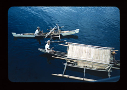 Photograph of two canoes with men from the George Grace Linguistic Research Collection