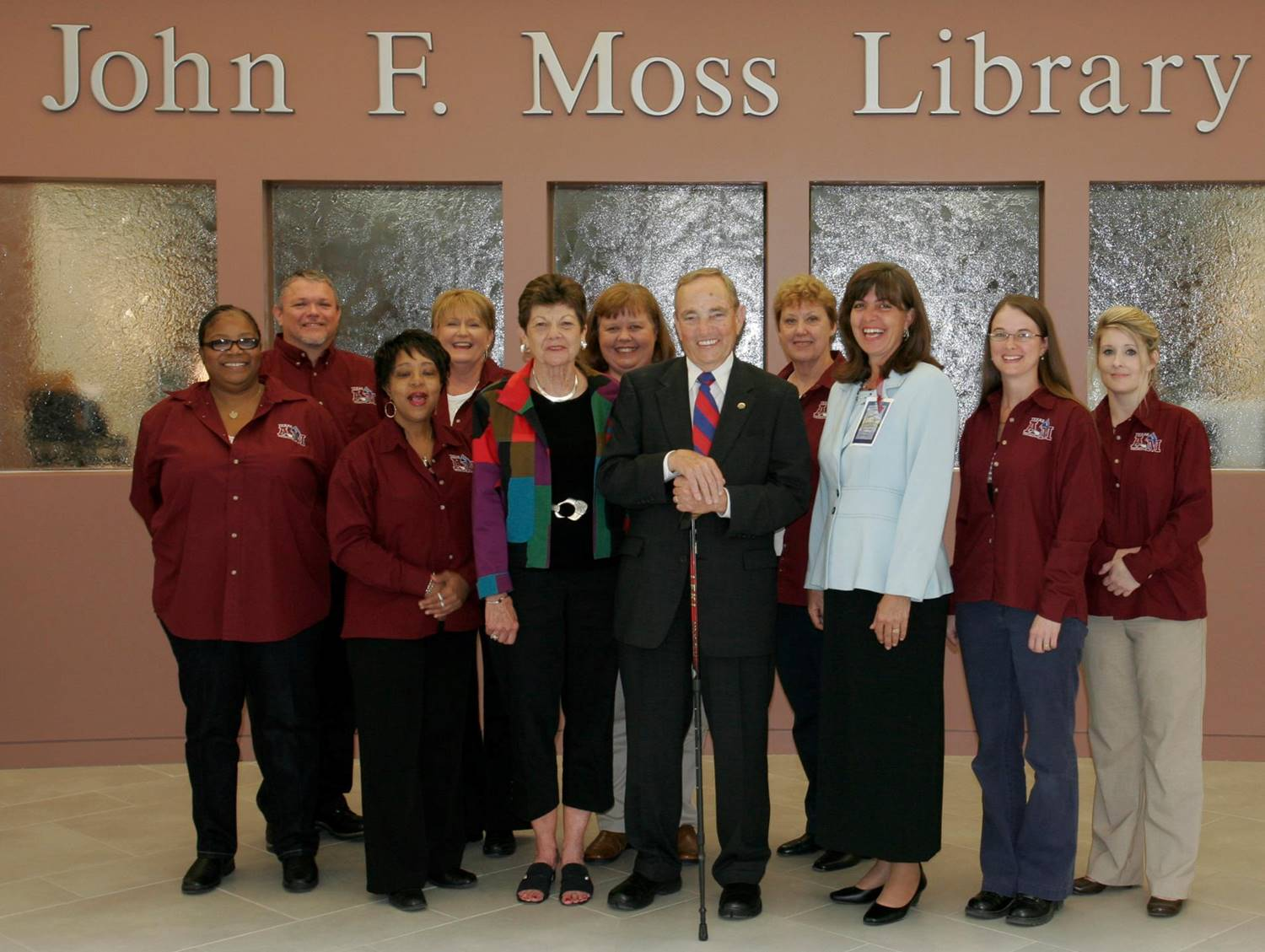 Photo of library staff in front of John F Moss Library with Mr. & Mrs. John F. Moss