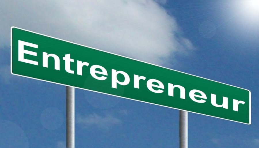 Road sign with the word Entrepreneur written in white on a green background set against the sky.