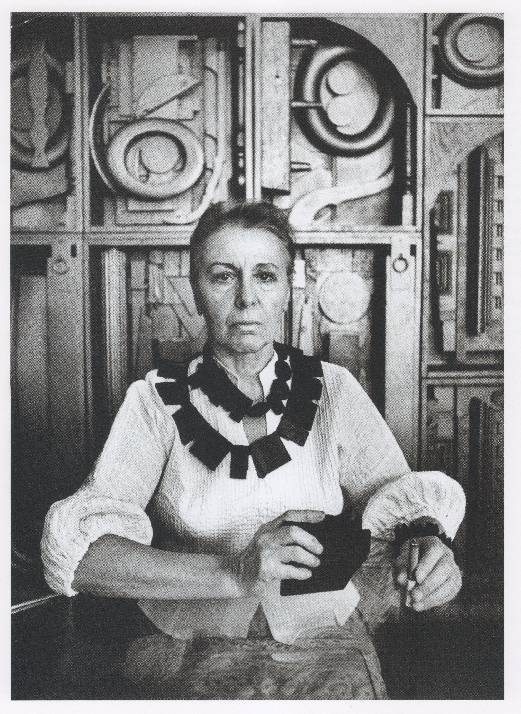 B/w photo of Louise Nevelson, posed before one of her assemblage sculptures.