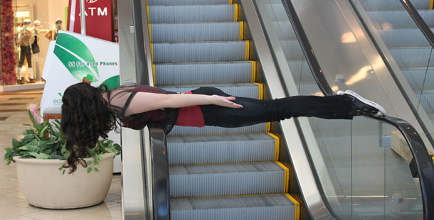 woman laying across the railings of an escalator