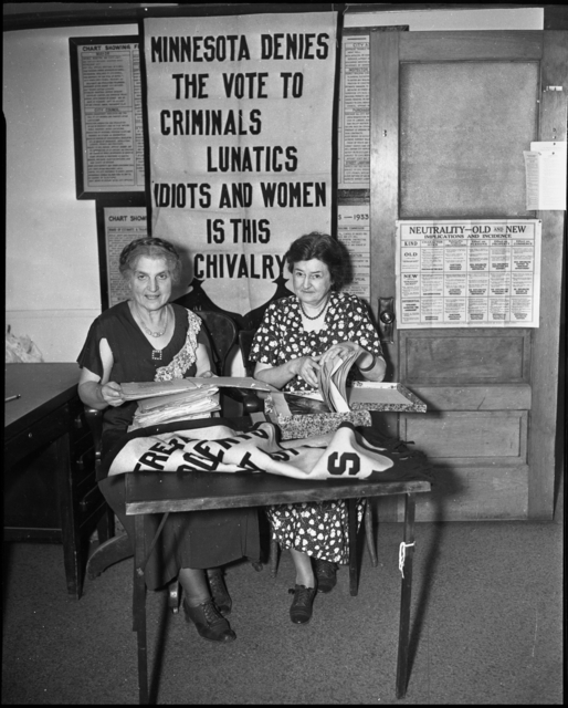 Women seated in front of early suffrage banner, date unknown.