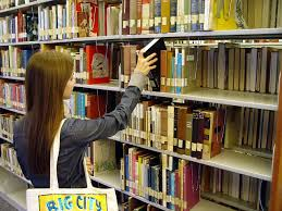 Student grabbing a book from the library's bookshelves