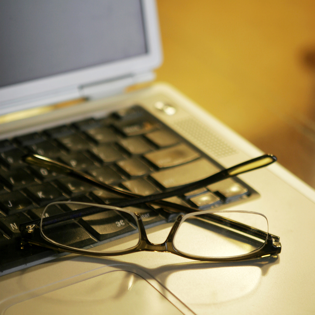 laptop with glasses sitting on the keyboard