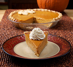 Pumpkin pie with separated slice on plate