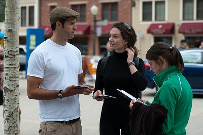 Three people with notebooks standing outside and talking