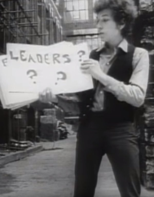 "Bob Dylan holding sign reading ""Leaders ? ?"""