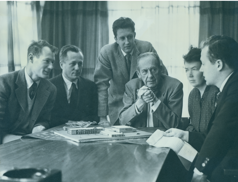 black and white photo of The Architects' Collaborative group arranged around a table with an architectural model, with Walter Gropius seated at the center
