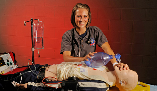 Picture of a women practicing using a breathing bag on a dummy