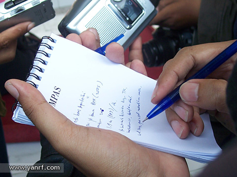 Person writing notes in a notepad