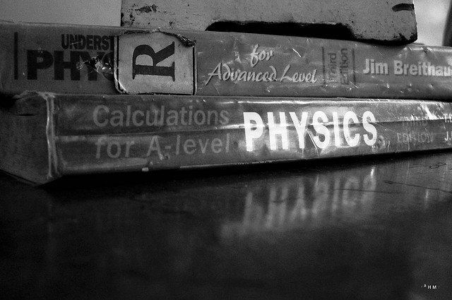 """a few physics books lying around the lab. on top of it is the base of a stand which is used to clamp stuff."""