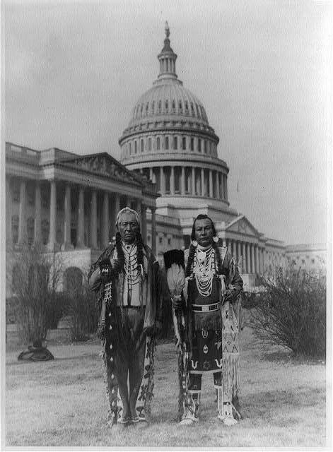 1927 black and white photograph of Native American chiefs Frank Seelatse and Chief Jimmy Noah Saluskin of the Yakima tribe posed, full-length, standing, facing front, with the U.S. Capitol behind them.
