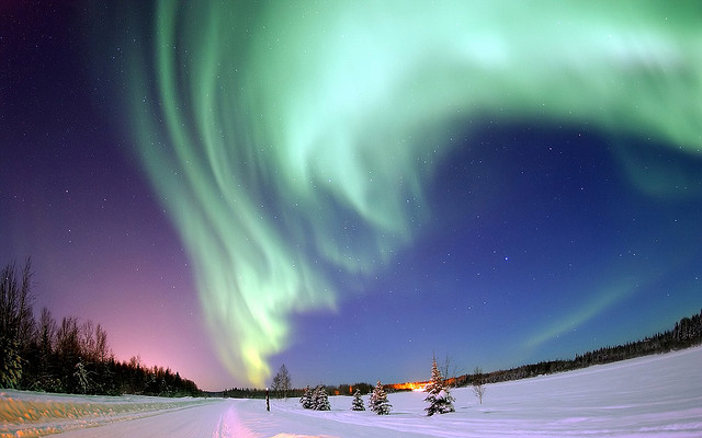 The Aurora Borealis pictured as a green cloudy trail across a purple sky at dawn or dusk.