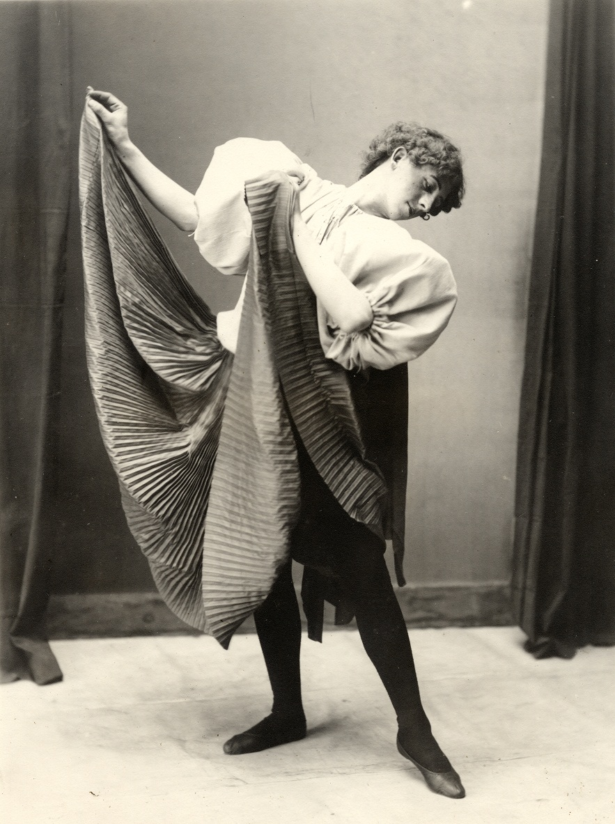 man costumed as a female dancer, posed with skirt held and head turned aside before a curtained wall; identified as Frank Lee