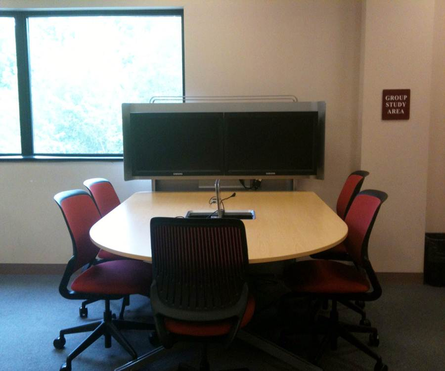 Photo of large computer screen on a table with chairs.