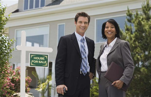 Two realtors standing in front of a house with a for sale sign.
