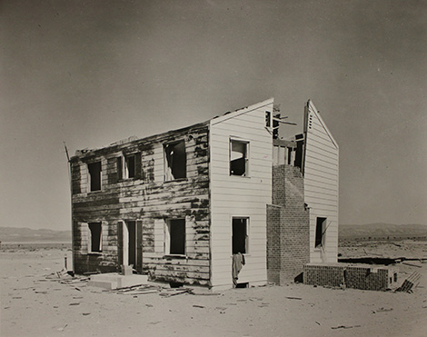 "photograph of house in ""Survival Town,"" which was built in Nevada to test the effects of a nuclear blast on buildings."